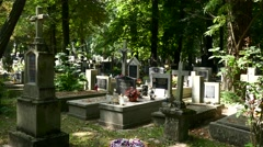 A pan across the graves in a Christian cemetery with shadows and highlights Stock Footage