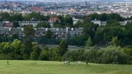 Couple sitting on top of a hill with a good view to the city and looking around Stock Footage