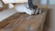 Closeup of a man hammering a used nail into old boards Stock Footage