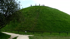 A pan to a grassy hill mound with people standing on top of it Stock Footage