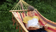Boy Reads a Book While Lying in a Hammock Stock Footage