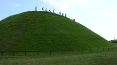 Group of unrecognized people walking down a grassy hill mound Stock Footage