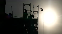 Silhouette construction workers building house using crane and scaffolding Stock Footage
