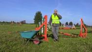 Horse handler with wheelbarrow and smart phone Stock Footage