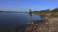 Man with spinning at the lake Stock Footage