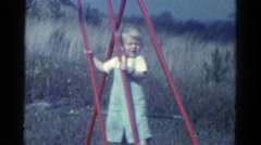 1959: child playing on a red swing set CATSKILL GAME FARM, NEW YORK Stock Footage