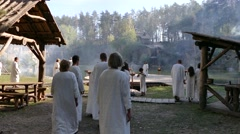People from religious community in white tunics gather for ritual Stock Footage