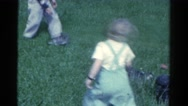 1959: kids outside in the yard playing with two cute puppies CATSKILL GAME FARM Stock Footage