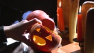 Put vampire fangs teeth in Halloween pumpkin mouth, table with candles Stock Footage