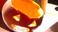 Put candle in Halloween Jack O' Lantern with vampire fangs in lamp light Stock Footage