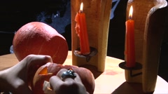 Put vampire teeth in Halloween pumpkin mouth, wooden table with candles Stock Footage