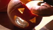 Halloween Jack O' Lantern with vampire teeth and fangs in the dark and light Stock Footage