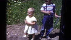 1959: two adorable children standing outside in a dirt patch CATSKILL GAME FARM Stock Footage