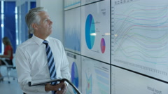 4K Portrait smiling businessman standing next to video wall with graphs & data Stock Footage