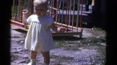 1959: a cute toddler in a yellow dress outside attempting to walk CATSKILL GAME Stock Footage