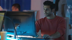 4K Young creative computer game designer working with colleagues in dark office. Stock Footage