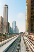Dubai's metro rail line, with ultra modern highrise buildings on either side. Stock Photos