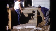 1960: two men at work at entrance of a house where a cat is at the entrance Stock Footage