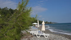 The sea, stones, sun loungers and deck chairs on the beach in Greece Stock Footage
