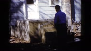 1960: man hoses off his porch WAUCONDA, ILLINOIS Stock Footage