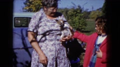 1960: older woman and girl petting dog carried in woman's curved arm  Stock Footage