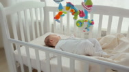 Cute baby lying in cradle with spinning toy carousel Stock Footage