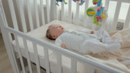 Cute baby boy relaxing in white wooden cradle near big window. Camera zooms i Stock Footage