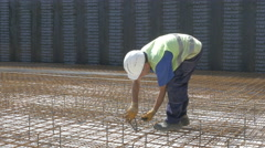 Construction worker tied  reinforcing mesh at building site by Sheyno. Stock Footage