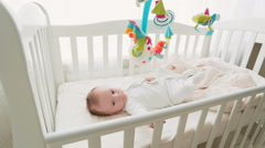 Cute 3 months baby boy lying in crib and looking at toy carousel Stock Footage