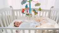 Cute 3 months old baby lying in white wooden crib next to big window Stock Footage