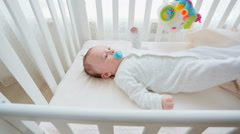 Dolly shot of cute 3 months old baby boy lying in white wooden crib with toy  Stock Footage