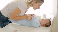 Beautiful young mother undressing her baby son lying on changing table Stock Footage