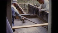 1960: the mason finishing the flooring and two men watching beside WAUCONDA Stock Footage