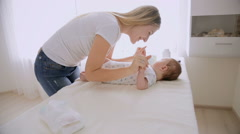 Young caring mother talking and playing with her baby boy lying on changing t Stock Footage
