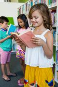 Elementary students reading books in school library Stock Photos