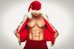 Sexy. Young muscular man wearing Santa hat demonstrate his Stock Photos