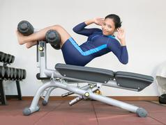 Woman practicing sit-ups on exercise machines at the gym Kuvituskuvat