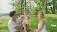 CLOSE UP: Joyful young family with baby girl and small dog playing in park Stock Footage