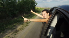 Young pretty girl leaning out of car window dancing and singing, 4k Arkistovideo