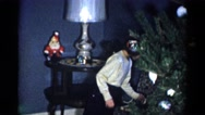 1959: a young girl and a smaller child hang ornaments on a christmas tree Stock Footage