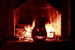 Halloween creepy pumpkin fireplace with fire, isolated in the red dark Stock Photos