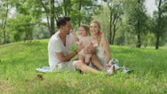 CLOSE UP: Adorable parents with beautiful baby girl sitting on blanket in park Stock Footage