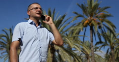 Casual Business Man Talking on Mobile Phone Tropical Island Exotic Palm Tree Day Stock Footage