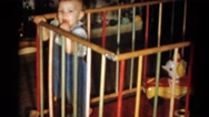 1959: a baby in overall peering over the railing of a crib like enclosure Stock Footage