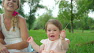 CLOSE UP: Sweet cheerful baby daughter playing in park and waving with straw Stock Footage