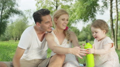 CLOSE UP: Adorable baby girl bringing bottle of water for her loving parents Stock Footage