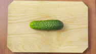 Woman cutting cucumber in the kitchen. wooden plank Stock Footage