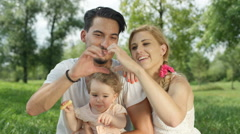 CLOSE UP: Mother and father holding baby girl in lap and making heart with hands Stock Footage