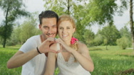 CLOSE UP: Adorable young couple sitting in park and making heart with fingers Stock Footage