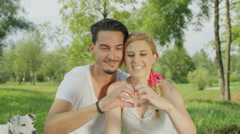 CLOSE UP: Young couple in love sitting in park and making heart with fingers Stock Footage